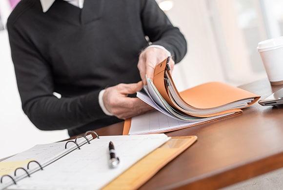 Ein Mann blättert durch Unterlagen