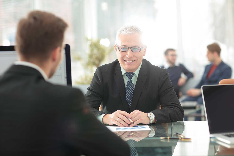 zwei Männer unterhalten sich an einem Tisch über Artikel 14 der DSGVO