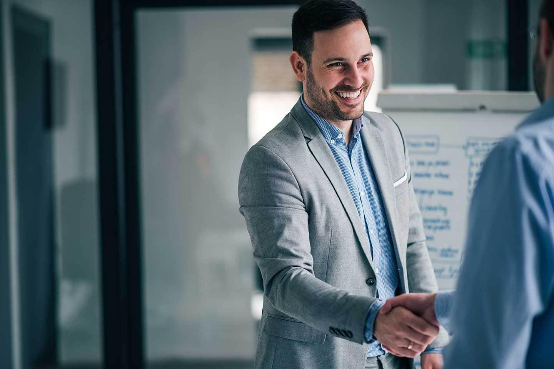 Ein Mann, der jemanden die hand gibt und über die Pflichte eines Datenschutzbeauftragten im Unternehmen reden