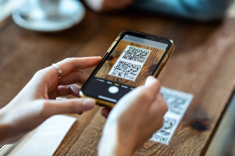 Ein Handy scannt einen QR-Code zur Abfrage des Impfstatus.