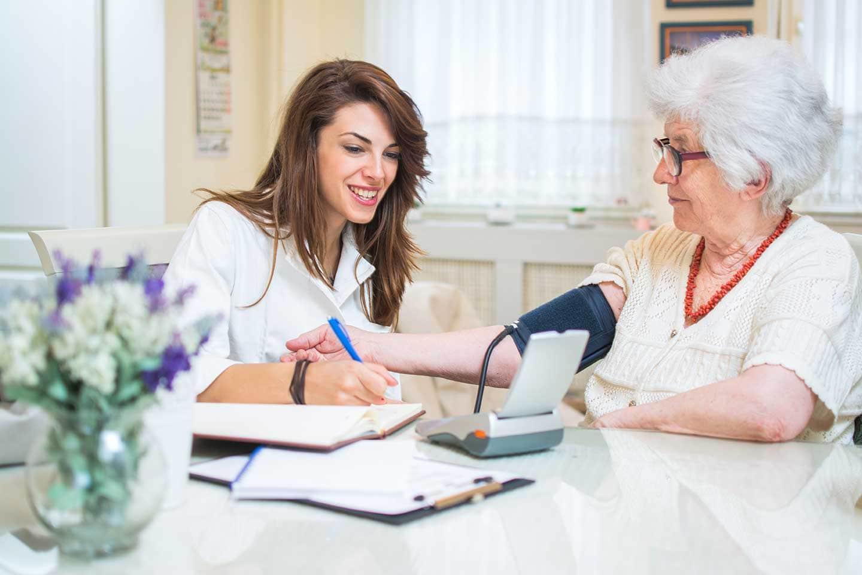 Eine Pflegerin erklärt einer Frau den datenschutz in der pflege
